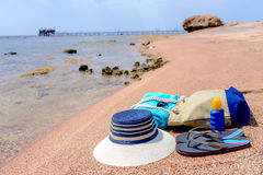 Beach gear on a sandy tropical beach. Beach gear arranged neatly at the waters edge on a sandy tropical beach with a sunhat, bag, slip slops, towel, sunglasses Royalty Free Stock Photography