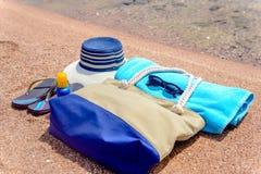 Beach gear on a sandy tropical beach. Beach gear arranged neatly waters edge sandy tropical beach  sunhat, bag, slip slops, towel, sunglasses suntan lotion Royalty Free Stock Image