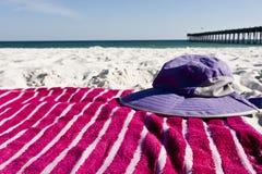 Beach Gear. Beach towel and sun hat lay on white sand Stock Image