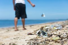 A man casually throws garbage on the ground, adding to the large amount of litter at the beach stock photography