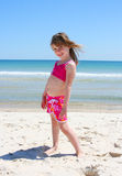 Beach girl. Girl playing in the sand at the beach royalty free stock image