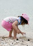 Beach Girl. A young girl plays on a pebble beach royalty free stock images