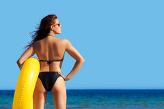 Beach Girl Bronzed Backs. Summertime Colors. Beautiful young woman backs. Beach girl in bikini with yellow giant float in the seashore enjoying the view. Summer Royalty Free Stock Images