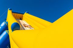 Beach Girl Fast Ride High Water Slide. Beach teenager girl thrill fast exciting ride going down high water slide slip way air inflated tall structure for fun stock photos