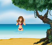 A beach with a girl in her violet bikini Stock Images