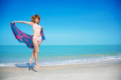 Beach girl holding scarft jumping. A girl in bikini holding floral scarft jumping by the beach Royalty Free Stock Image