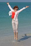 Beach Girl Jumping. With joy by edge of the water royalty free stock image