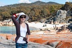 Beach girl with orange lichen on granite rocks Royalty Free Stock Photo