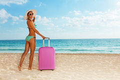 Beach girl with pink luggage near the sea Royalty Free Stock Photos