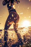 Beach girl stand in splashes in water. Model hold small fins in hands wearing bikini bottom and rashguard on top of her body. Bright Sunset sunlight on clear royalty free stock photos