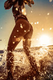 Beach girl stand in splashes in water royalty free stock photo
