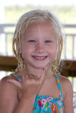 Beach Girl Using Hang Loose Hand Gesture. Five year old blond little girl smiling with wet hair and bathing suit showing a Hang loose hand gesture with her hand Stock Image