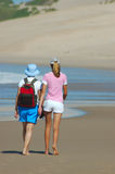 Beach girls. Two young women are walking in the sand on the beach together close to the water Stock Photo
