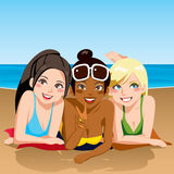 Beach Girls. Three girl friends happy together sunbathing lying on the beach looking at front Stock Photo