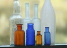 Beach glass bottles on a windowsil. Royalty Free Stock Photos