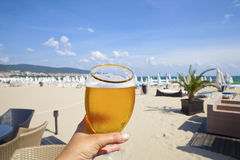 Beach Glory. Holding beer glass at beach resort Royalty Free Stock Images