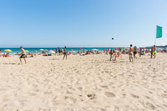 Beach-goers and group of men playing football  enjoyng hot summe Stock Image