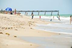 Beach Goers near Ocean Pier. Sun bathers playing in surf near ocean pier extending into aqua blue water. Vero Beach, Florida Stock Photos