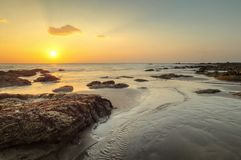 Beach in golden sunset light during low tide showing stream of w. Ater and rocks covered with sea algae. Kantiang Bay, Ko Lanta, Thailand Stock Photos