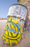 Beach Graffiti Trash Can. Trash can and palm tree at the beach covered in graffiti Stock Images