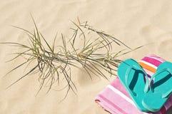 Beach grass towel and flip-flops. Stock Photography