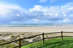 Beach with grass, wooden fence and industrial port. Sea with waves and cloudy sky, Sabon, Spain. Sabon, La Coruña Province, Rias Altas, Galicia, Spain. Beach royalty free stock image