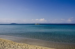 Beach in Greece. View on the little island, Aegean sea, Sithonia, Halkidiki, Greece Royalty Free Stock Images