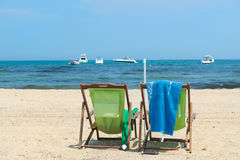 Beach with green chairs and boats in water Stock Photos