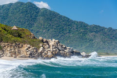 Beach and Green Hills. Beach in Tayrona National Park with beautiful green hills in the background in Colombia Stock Photo