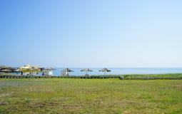 Beach. Green lawn and beach umbrellas, Beach Stock Photography