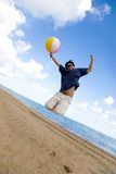 Beach guy jumping with ball Stock Photos