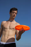 Beach guy playing with frisbee Stock Images