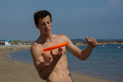Beach guy reverse frisbee trick. Guy making a trick with a frisbee Royalty Free Stock Image