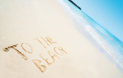 Beach with hand written text TO THE BEACH and sea Stock Image