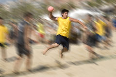 Beach handball player jumping with ball. Beach handball player trying to score a goal Royalty Free Stock Photo
