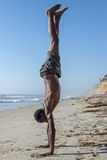 Beach handstand. Side view of tall lean shirtless African American man performing handstand on California beach under clear blue sky Stock Image