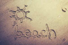 Beach handwritten in the sand of the beach with a lovely sun stock illustration