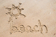 Beach handwritten in the sand of the beach with a lovely sun stock photography
