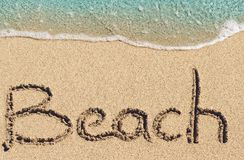 Beach handwritten on sand. Word Beach handwritten on sand of tropical beach Royalty Free Stock Images
