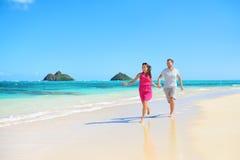 Beach happy couple on running having fun on Hawaii Stock Images