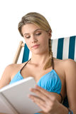 Beach - Happy young woman in bikini with book Stock Images
