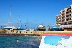 Beach and harbour, Marsalforn, Gozo. View of the beach with boats and yachts in the harbour to the rear and a Marsalforn Bay plan in the foreground, Marsalforn Royalty Free Stock Photo