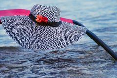 Beach hat black and white with fresh flowers lying on a beach chair handrails in the water. Natural sea summer background royalty free stock photography