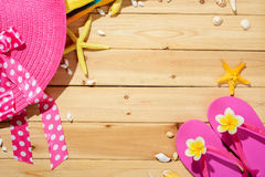 Beach hat and flip-flops. On the wooden board royalty free stock images