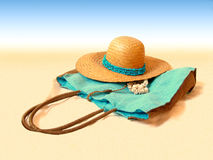 Beach hat and handbag. On sand with some shells Royalty Free Stock Photography