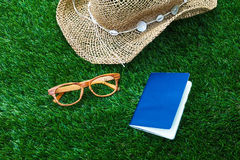 Beach hat ,Passport and vintage glasses on green grass Royalty Free Stock Image