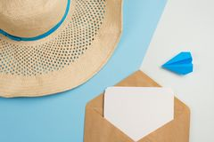 Beach hat, postcard in the envelope and the plane on a blue background. concept of flight on vacation and travel royalty free stock images