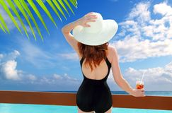 Beach hat rear view woman cocktail tropical beach. Black swimsuit Royalty Free Stock Photography