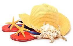 Beach hat, red flip flops with starfishes and a seashell Stock Photos