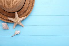 Beach hat with seashells on blue wooden table stock image